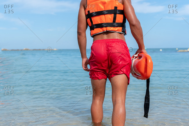 Back view of unrecognizable young lifeguard in bright life vest carrying torpedo rescue buoy on rippled sea
