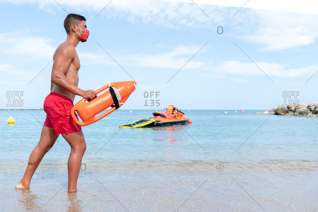 Side view of anonymous male lifeguard in shorts and mask walking on sandy sea shore with torpedo rescue buoy