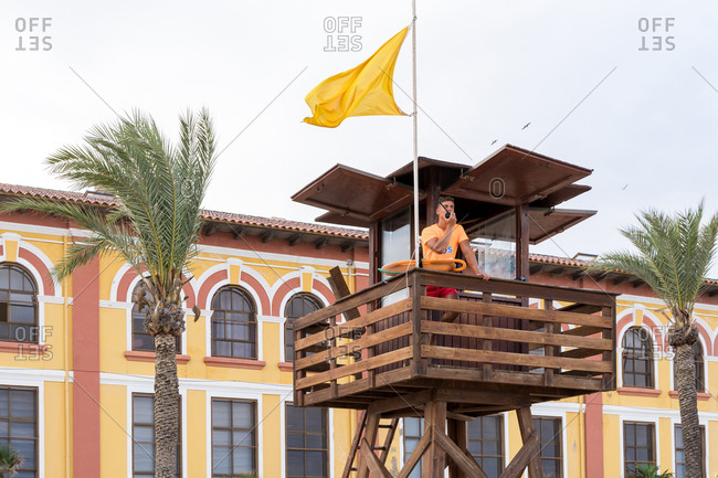 Young male employee on lifeguard tower speaking on walkie talkie radio above ocean
