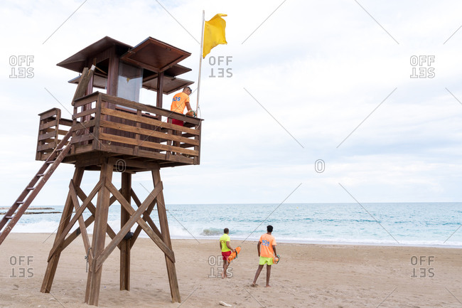 From below back view of unrecognizable male employee on lifeguard tower speaking on walkie talkie radio above ocean
