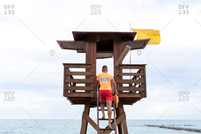 Low angle back view of unrecognizable barefoot lifeguard ascending ladder of wooden tower near sea under cloudy sky