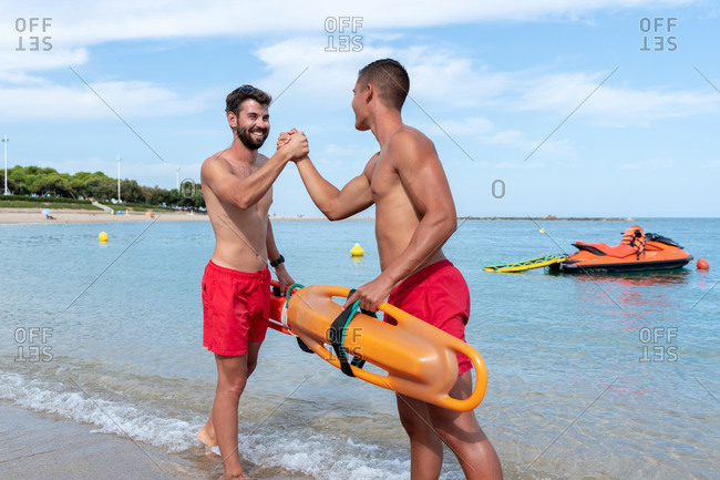 Happy young male workers in shorts with torpedo rescue buoy shaking hands on ocean coast while looking at each other