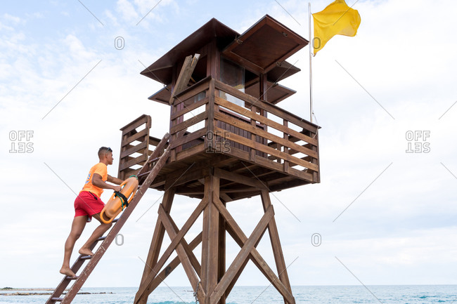 Low angle side view of unrecognizable barefoot lifeguard ascending ladder of wooden tower near sea under cloudy sky