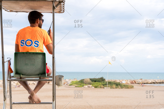 Back view of unrecognizable male employee on lifeguard tower speaking on walkie talkie radio above ocean