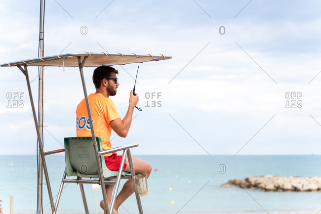 Side view of unrecognizable male employee on lifeguard tower speaking on walkie talkie radio above ocean