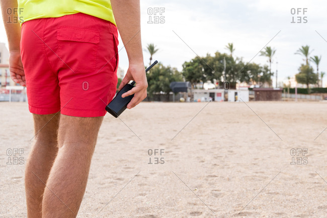 Cropped unrecognizable male employee in colorful outfit holding walkie talkie radio standing on sandy sea shore