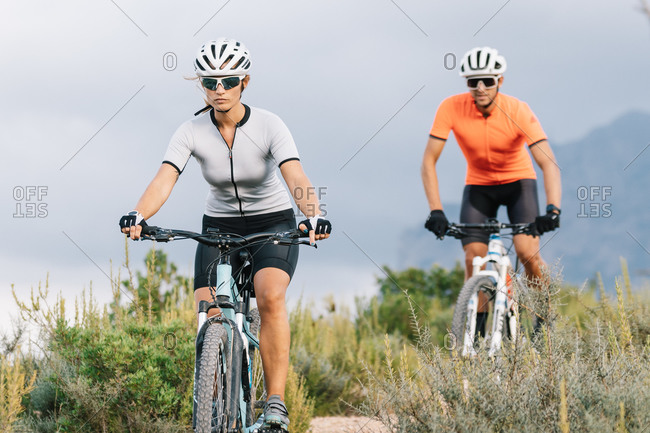 Serious professional bicyclists in helmets and sunglasses riding uphill in highlands during training in summer