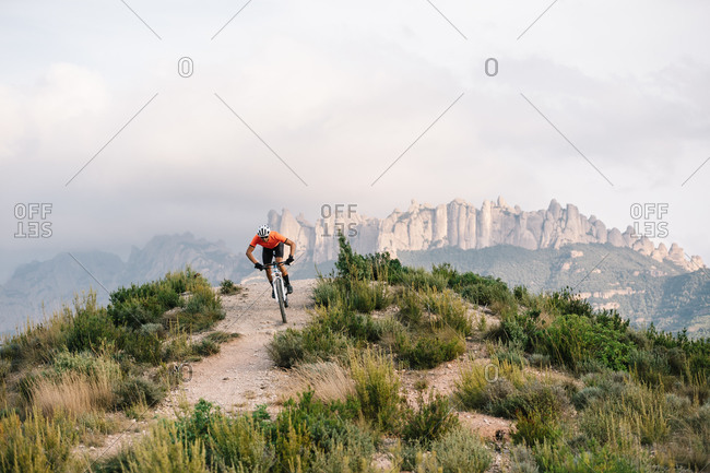 Male cyclist in helmet and sunglasses riding mountain bike among green hills in summer day
