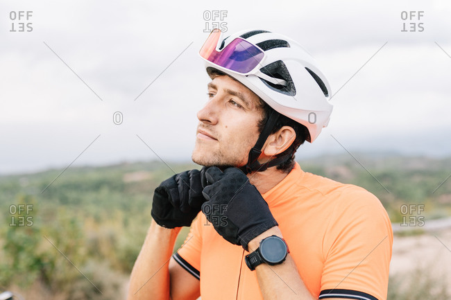 Calm male bicyclist standing in nature and putting on protective helmet while preparing for riding bicycle and looking away