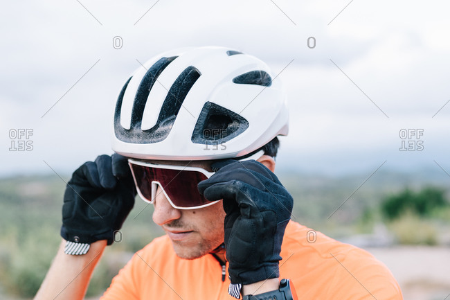 Confident male bicyclist in helmet putting on protective sunglasses while standing in nature and preparing for riding