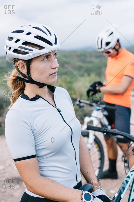Side view of confident female bicyclist wearing helmet standing in nature near bike on background of male cyclist and looking away