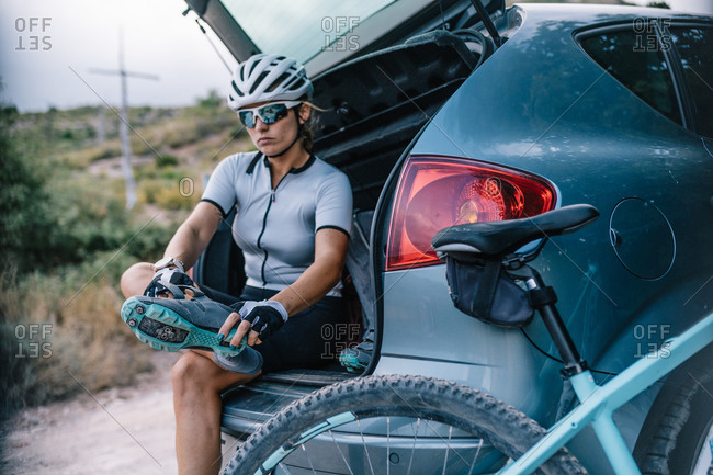 Confident female bicyclist in helmet and sunglasses sitting in trunk of car and preparing for ride while putting on boots and looking at camera