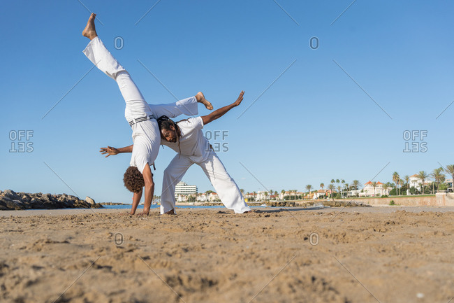 Side view of ethnic african american male partners in white wear fighting while practicing martial art on sea beach