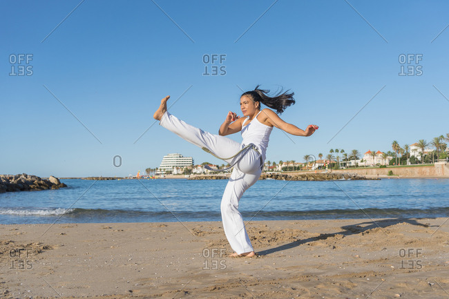 Young focused ethnic female in capoeira clothes showing balance trick while standing with raised arms on sandy shore near ocean and looking away