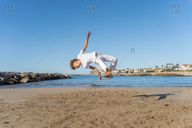 African american mixed race barefoot teen boy jumping in air with raised leg and arms while practicing brazilian martial art