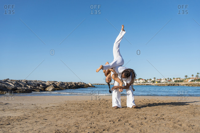 Ethnic african american male and caucasian female in white wear fighting while practicing martial art on sea beach