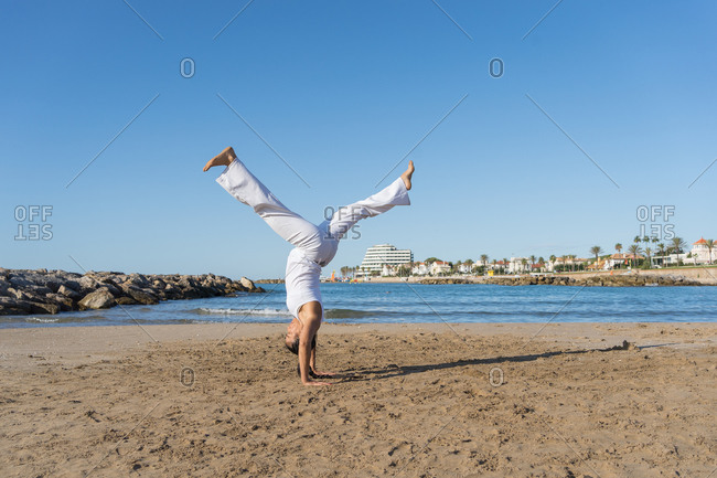 Young focused ethnic female in capoeira clothes showing handstand balance trick on sandy shore near ocean