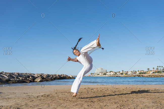 Young focused ethnic female in capoeira clothes showing balance trick while standing with raised arms on sandy shore near ocean and looking at camera