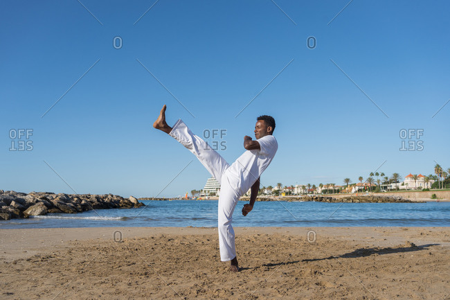African american barefoot man jumping in air with raised leg and arms while practicing brazilian martial art on sandy coast near ocean