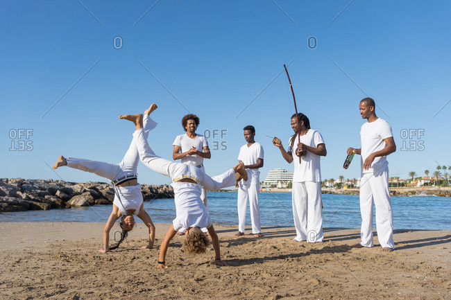 Group of anonymous barefoot black partners in white clothes practicing martial art on sandy beach under blue sky