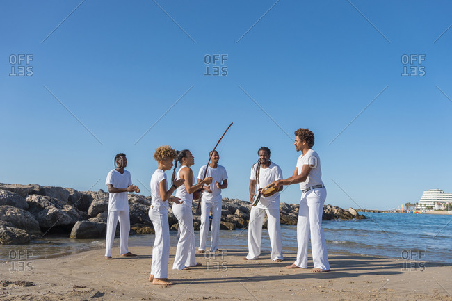 Cheerful multicultural group of people playing musical instruments near woman with archery bow during capoeira performance under blue sky