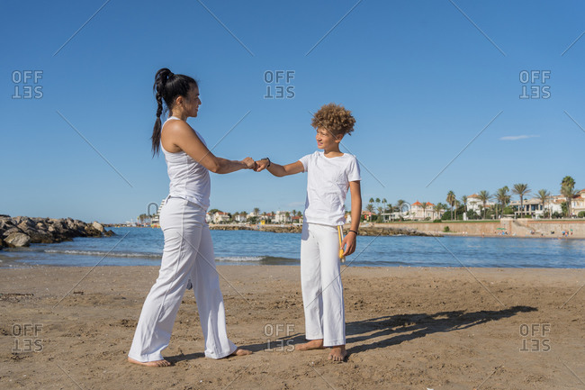 Content barefoot brazilian woman and adolescent in capoeira apparel bumping fists while looking at each other and standing on sandy ocean shore