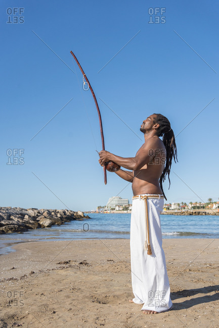 Side view of masculine african american male in capoeira clothes with naked torso standing on sandy ocean coast with archery bow and looking up