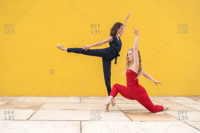 Full body side view of graceful slim young women in colorful clothes performing modern expressive dance against yellow wall