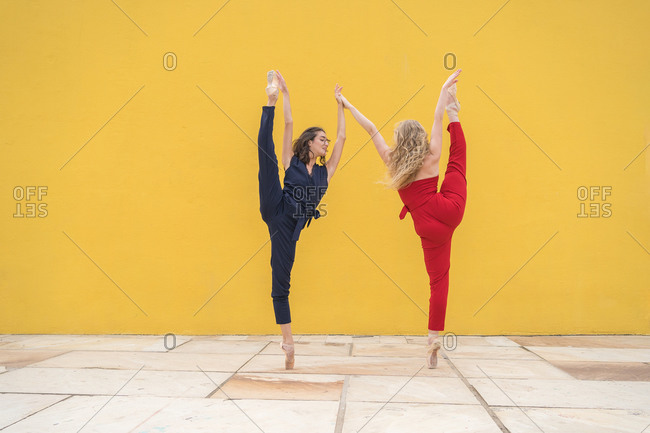 Full body side view of talented young female dancers in colorful outfits performing dancing movement with legs raised against yellow wall