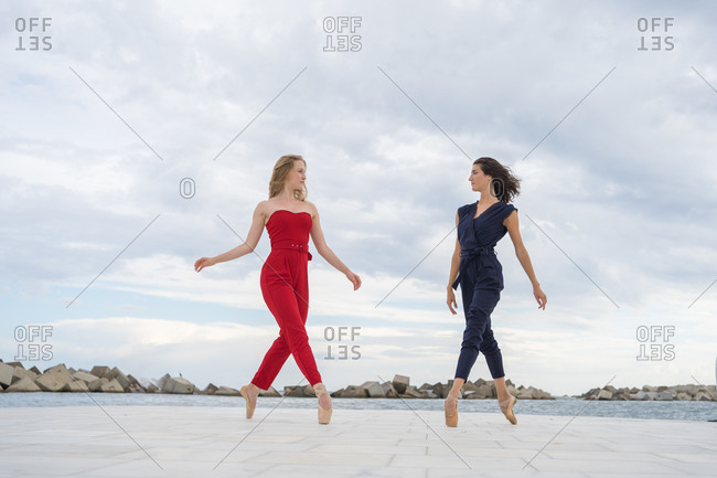 Low angle full length of stylish slim female artists dancing on tiptoe on paved waterfront against overcast sky