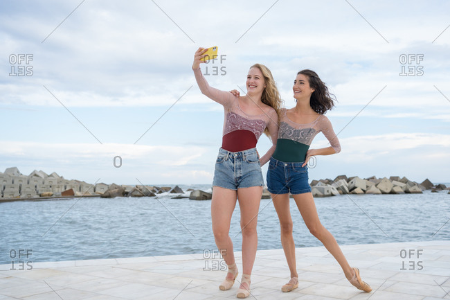 Full body of cheerful young slim women in similar outfits and ballet shoes standing on waterfront