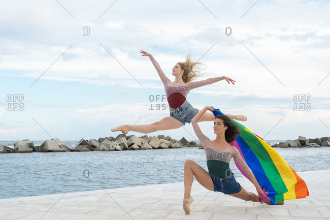 Full body side view of modern talented female dancers performing energetic dance movements with rainbow flag on waterfront near sea