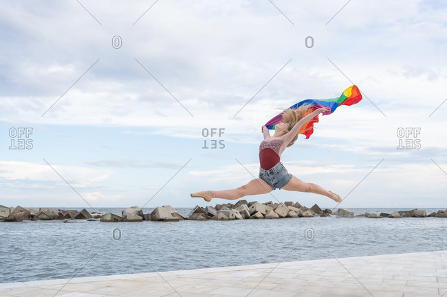 Full body side view of modern talented female dancer performing energetic dance movements with rainbow flag on waterfront near sea