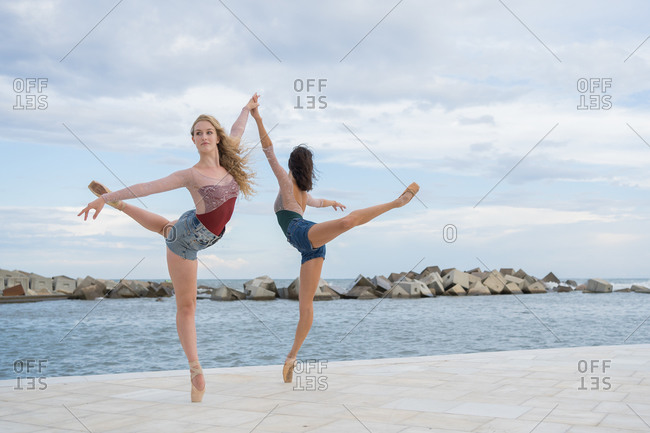 Full body side view of elegant professional modern ballet dancers balancing on tiptoe while performing sensual dance near sea against cloudy sky