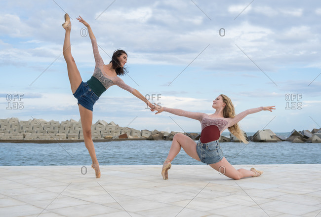 Full body side view of inspired talented young female dancers performing expressive dance movement together on paved waterfront near sea