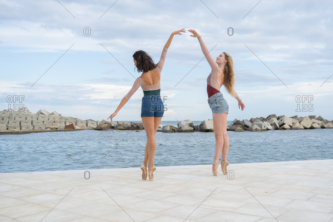 Full body side view of professional female dancers performing graceful pose on paved embankment near sea water
