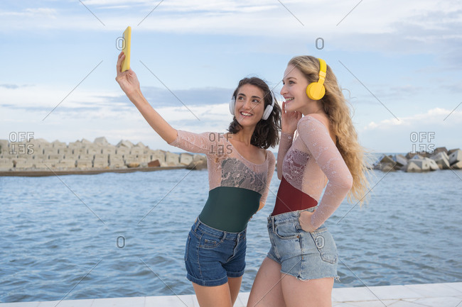 Joyful young girlfriends taking selfie with smartphone while having fun and listening to music with headphones on seashore