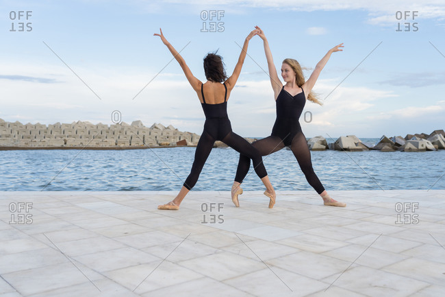 Full body of modern female ballet dancers in black leotards performing sensual dance together on paved embankment near sea