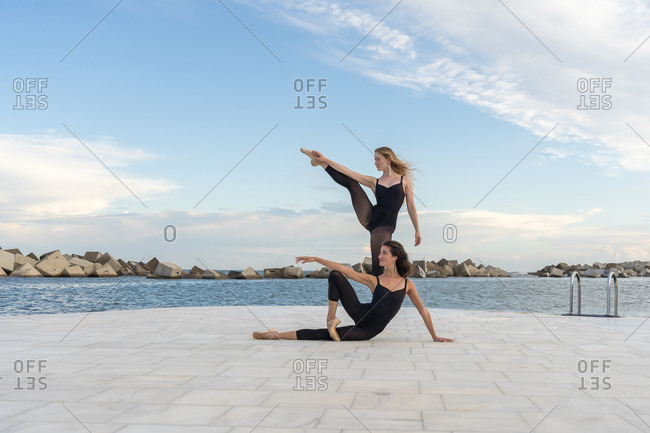Full length of creative young female dancers in black clothing performing various dance movements on waterfront near sea