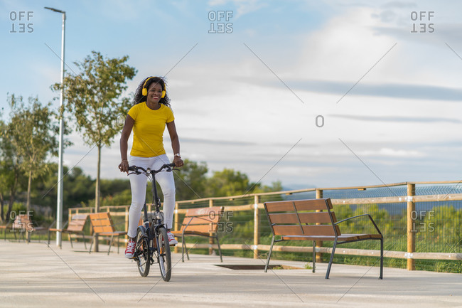 Delighted african american female listening to music in headphones and riding bicycle while looking forward and enjoying summer weekend in urban park