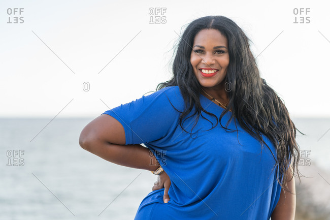 Young glad plump african american female in trendy clothes standing with hand on waist while looking at camera near ocean