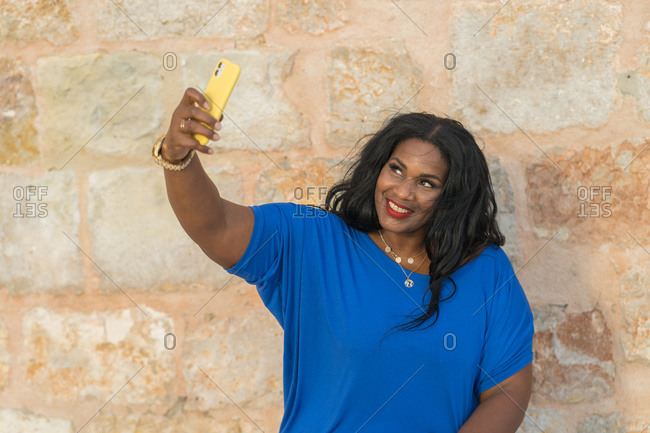 Young positive plump african american lady in elegant blue dress and wristwatch taking selfie with smartphone while sitting near stone wall