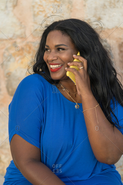 Young positive plump african american lady in elegant blue dress and wristwatch conversing on cellphone while sitting near stone wall and looking away