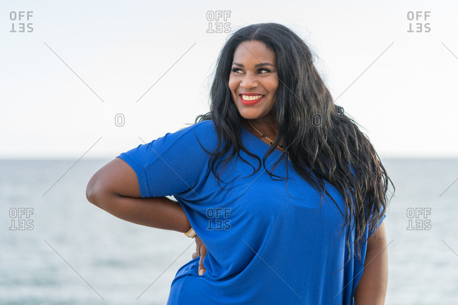 Young glad plump african american female in trendy clothes standing with hand on waist while looking away near ocean