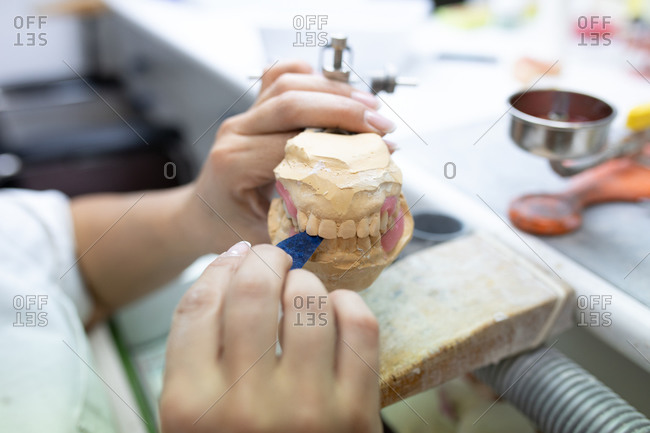 High angle side view of crop unrecognizable skilled dental technician using articulator while working with plaster cast in dentistry laboratory