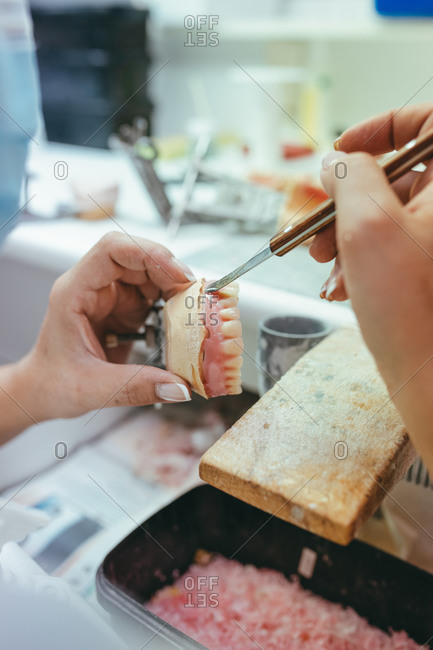 Unrecognizable female technician working in lab and using polishing machine for producing denture