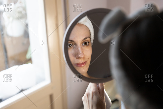 Crop young woman in white headband applying eyeshadow with hand and looking at reflection in mirror while sitting in front of large window
