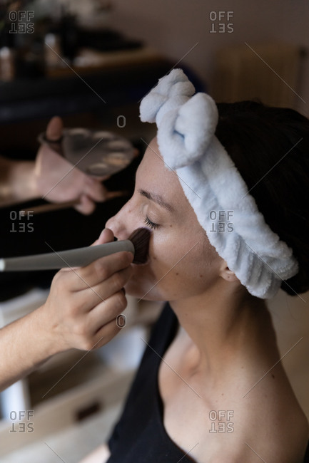 From above crop professional makeup artist using brush while applying foundation cream on calm female customer forehead sitting in salon with eyes closed