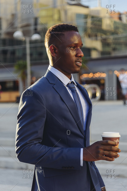Serious adult formally dressed african american male manager drinking takeaway coffee while standing against blurred urban background of modern city