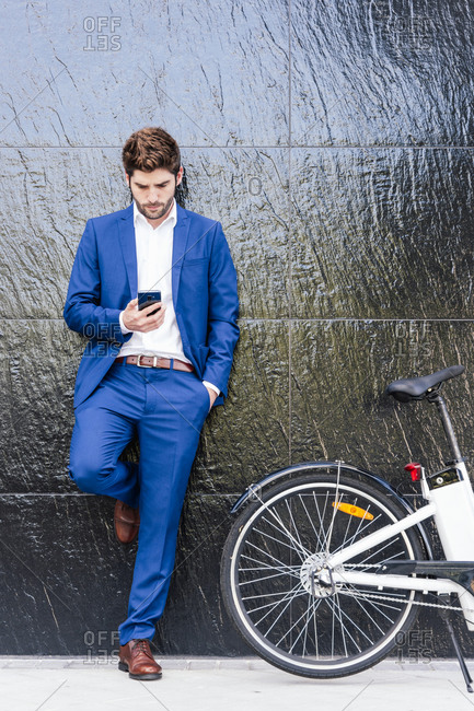 Serious male executive in formal suit leaning on wall while surfing internet on cellphone and standing with hand in pocket near electric bicycle